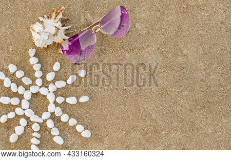Purple Sunglasses Lie On Sand Beach With Seashell And Sun Made Of White Stones. Concept Summer Holid