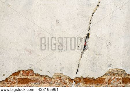 Rough Plastered Brick Wall With Cracks. Dirty Damaged Texture, Peeling Plaster, Damaged Wall. Vintag