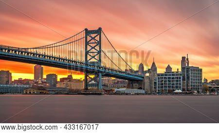 Philadelphia, Pennsylvania, USA skyline on the Delaware river with Ben Franklin Bridge at dusk.