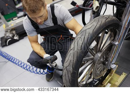 Man Repairman Inflating Motorcycle Tires In Auto Repair Shop