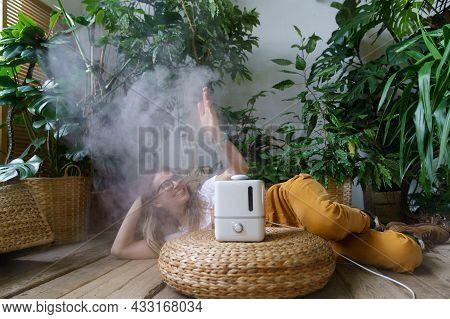 Cheerful Girl Gardener Enjoy Fresh Air Steam From New Humidifier Lying On Floor In Home Garden Surro