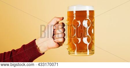 Oktoberfest. Man Hand With Glass Of Draft Beer With Foam. Fresh Cold Beer In Glass In Hand. Beer Pub