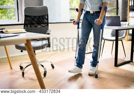 Worker With Crutches At Workplace Or Office. Handicap Rehabilitation Benefits