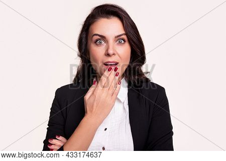 Amazed Adult Businesswoman In Black Suit And White Shirt Keeping Hand Near Mouth And Looking At Came