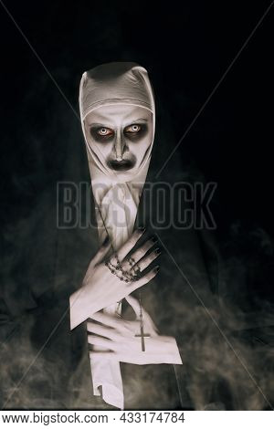 Halloween. Portrait of a scary devilish nun with bloody eyes looking at camera on a black background. Horrors.