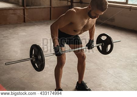 Muscular Shirtless Male Bodybuilder Doing Barbell Row Exercise With Heavy Barbell During Weight Trai