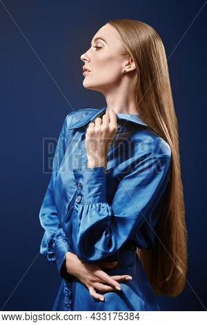 Beauty, Fashion shot. Sideview portrait of a beautiful fashion model girl with long straight hair posing in blue satin dress on a dark blue background.