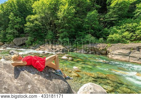 Woman Relaxing Sitting On The Rocks Of The Verzasca River. Verzasca Valley By Lavertezzo Town. Famou