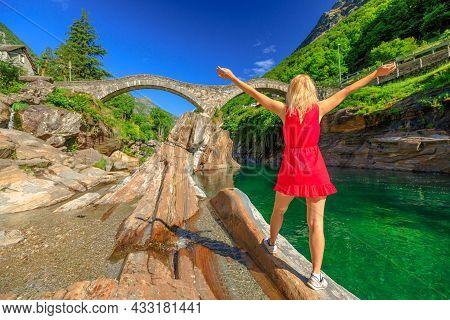 Woman By Roman Stone Bridge: Ponte Dei Salti Over Verzasca River. Verzasca Valley By Lavertezzo Town