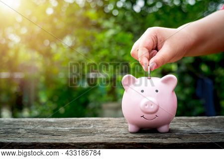 Little Boy Hand Putting Money Coin Into Piggy Bank For Saving Money,concept Financial Business Inves