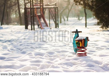 Playground In The Park In The Winter | Back View Photo Of Blue-red Rocker With Playground Climber Wi