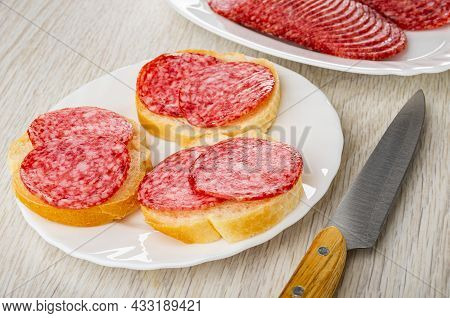 Slices Of Sausage Salami In Dish, Three Sandwiches In White Plate, Kitchen Knife On Wooden Table