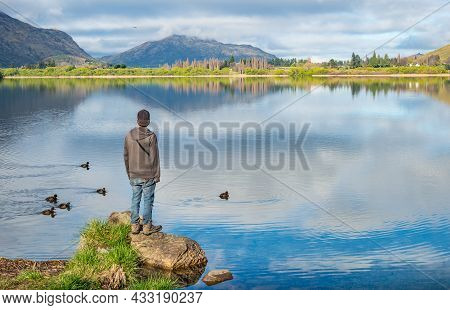 Man Looking To The Spectacular View Of Lake Hayes One Of The Most Photographed Lake In New Zealand,