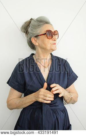 Indoors Portrait Of Beautiful Old Grandmother With Grey Hair And Fashionable Eyeglasses Wearing Dark