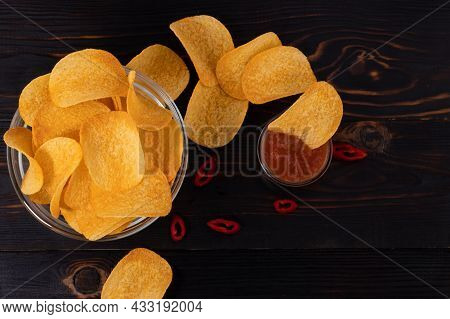 Potato Chips With Hot Peppers On A Wooden Background Top View