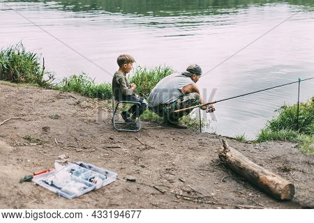 A Young Man Teaches His Children To Fish During A Family Vacation At A Camping Site. Hobbies, Vacati