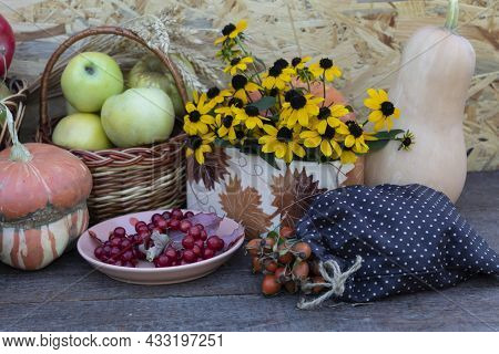 On The Table Is A Basket Of Apples, A Bouquet Of Yellow Flowers, A Plate With Viburnum Berries, A Ba