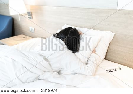 Asian Lady In White Long Arm T-shirt Pajamas Lie Prone, Lie On The Stomach In Bed With Tried And Exh