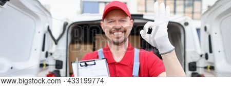 Male Courier Holding Delivery Receipt And Showing Okay Gesture Closeup