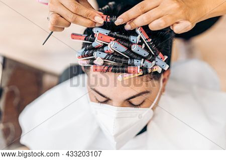 Profile Of A Blonde Hairdresser Arranging The Curls Of The Hair Of A Man Indoors
