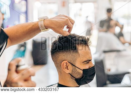 Barber Putting Lacquer On The Hair Of A Man Wearing A Mask In A Salon