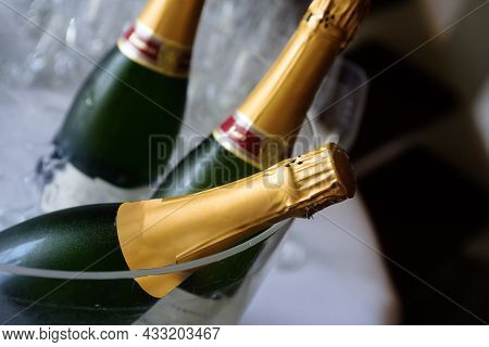 Closeup Of Champagne In Wine Chiller With Defocusses Champagne Glasses And Black Background