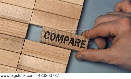 Compare Word Concept. Close-up Wooden Piece Blocks On The Table. Top View
