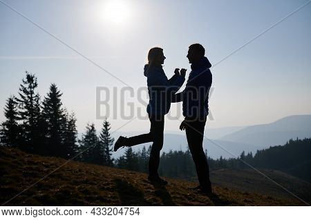 Silhouettes Of Girl Standing On Lawn With Two Arms Outstretched To Her Boyfriend With One Bent Knee