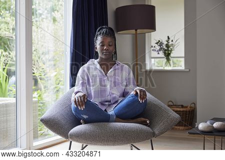 Peaceful Teenage Girl Meditating Sitting In Chair At Home
