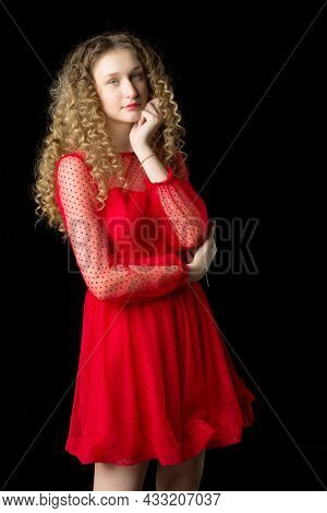 Portrait Of Thoughtful Girl In Short Red Dress. Charming Pretty Blonde Girl With Fluffy Wavy Hairsty