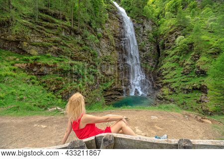 Woman Sitting By The Froda Waterfall Or Sonogno Waterfall Over The Riale Carded River In Sonogno Tow