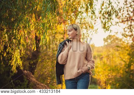 A Blonde Woman With A Short Haircut Walks Through The Forest In A Knitted Sweater And A Leather Jack