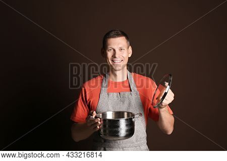 Happy Man With Cooking Pot On Brown Background