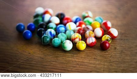 Many variations of vintage marbles. Beautiful vintage marbles rolled out on a old wooden table. Extremely shallow depth of field.