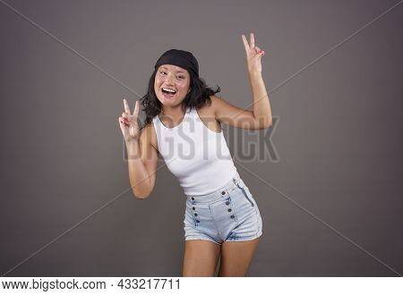 Pretty Chinese Girl With Bandana And Shorts, Making The Peace Sign Or Victory Sign, In Funny Pose An