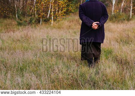 Defocus Freedom Old Woman, Female Person Walking In Autumn Meadow. Fall Dry Grass. Old People Leavin