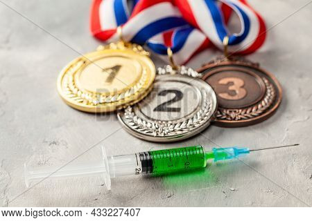 Doping For Athletes. Golds, Silver And Bronze Medal And Doping Syringe On A Gray Background