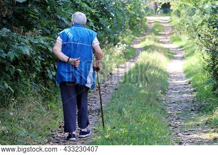 Old Woman Walking With A Cane On A Rural Street. Limping Person, Diseases Of The Spine, Life Of Elde