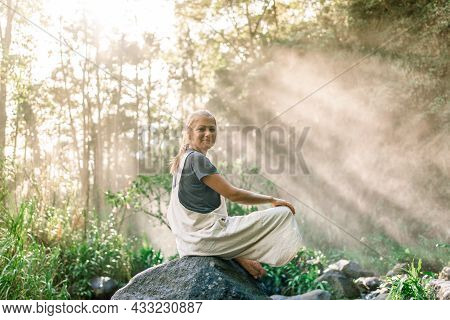 Woman Sitting With Her Legs Bent On A Rock In The Rainforest While The Rays Of Light Illuminate Her