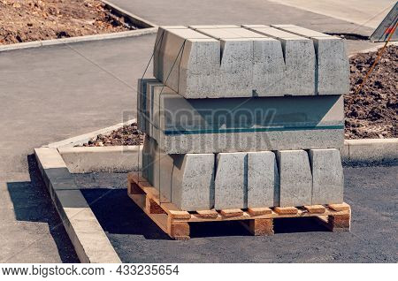 Curb Stone On Construction Site. Pallet With A Stack Of Concrete Curbstone. Road Repairs.
