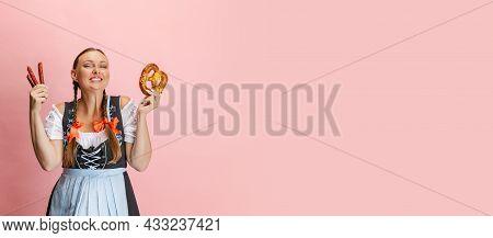 Adorable Oktoberfest Woman, Waitress Wearing A Traditional Bavarian Or German Dirndl Holding Bretzel