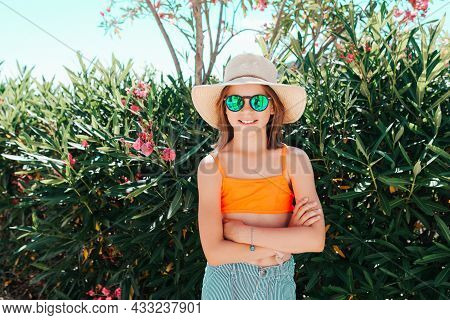 Little Smiling Playful Girl In A Straw Hat And Sunglasses Crossing Her Arms In Front Of Her - Lookin