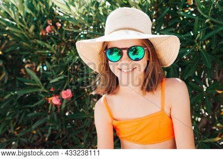 Little Smiling Playful Girl In A Straw Hat And Sunglasses - Looking Directly At The Camera - Against