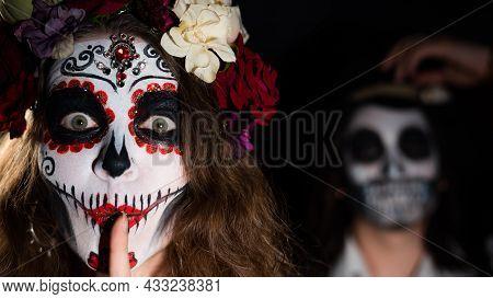 Woman In Santa Muerte Costume And Man In Skeleton Bodypainting For Halloween.