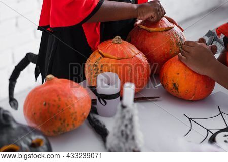 Partial View Of African American Kids Carving Pumpkins