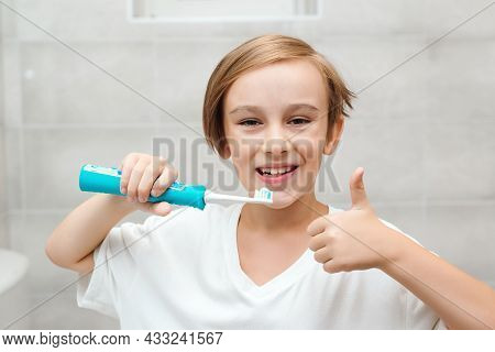 Smile Boy Cares About Health Of His Teeth. Kid Brushing Teeth With Electic Brush In Bathroom. Dental