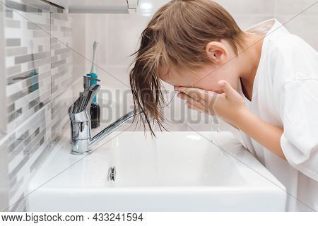 Preteen Boy Is Washed In A Wash Basin. Healthy Childhood And Lifestyle. Boy Washing Face In The Bath