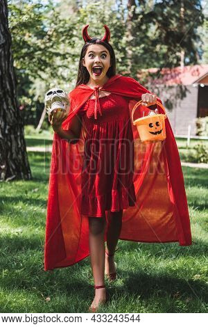 Astonished Girl In Demon Halloween Costume Shouting While Standing With Skull And Bucket Of Candies