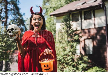 Astonished Child In Demon Costume Screaming While Holding Skull And Halloween Bucket Near Blurred Co
