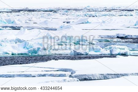 Pack ice, icebergs and ice floes of the arctic ocean, north of Svalbard. The snow covered blue glacial ice is an unspoilt wilderness but is fast melting due to climate change.